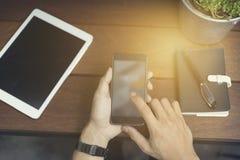 mężczyzna ręka używać smartphone z cyfrową pastylką Obrazy Stock