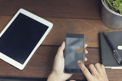 mężczyzna ręka używać smartphone z cyfrową pastylką Obraz Stock
