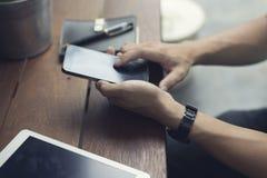 mężczyzna ręka używać smartphone z cyfrową pastylką Zdjęcia Stock