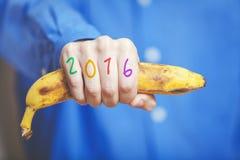 Mężczyzna ręka w koszulowym mienie bananie Liczby na palcach Fotografia Royalty Free
