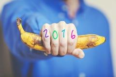 Mężczyzna ręka w koszulowym mienie bananie Liczby na palcach Obrazy Royalty Free