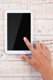 Mężczyzna ręka wskazuje pastylka telefon na drewno stołu tle Fotografia Stock