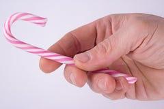 Mężczyzna ręka z cukierek trzciną Zdjęcia Stock