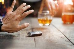 Mężczyzna ręka z samochodu kluczem na stole odrzuca pijący alkohol obraz royalty free