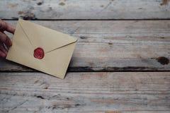Mężczyzna ręka z wosk foki kopertą na drewnianym tle Zdjęcie Royalty Free