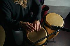 Mężczyzna ręki bawić się muzykę przy djembe bębenami Zdjęcia Stock