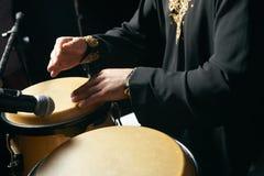 Mężczyzna ręki bawić się muzykę przy djembe bębenami Obrazy Stock