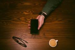 Mężczyzna ręki dotyk na ekranie telefon komórkowy na drewnianym stole symbolicznych grup biznesowych sytuacj ludzie Fotografia Royalty Free