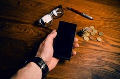 Mężczyzna ręki dotyk na ekranie telefon komórkowy na drewnianym stole symbolicznych grup biznesowych sytuacj ludzie Obraz Royalty Free