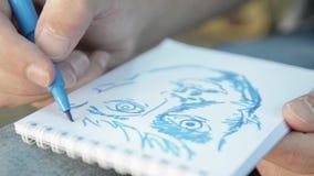 Mężczyzna ręki malują twarz błękitnym markierem na papierowej notatnik ostrości wewnątrz dzień z bliska zbiory wideo