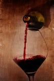 Mężczyzna ręki mienia butelki dolewania czerwone wino podsadzkowy szkło na arty tle Zdjęcia Stock