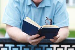 Mężczyzna ręki mienia czytanie w parku i książka Zdjęcia Royalty Free