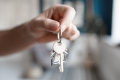 Mężczyzna ręki mienia klucz z domem kształtował keychain Nowożytny światło lobby wnętrze 100 rachunków pojęcia dolara dom robić h Fotografia Stock