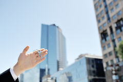 Mężczyzna ręki mienia klucze na tło budynkach biurowych, Obrazy Royalty Free