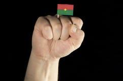 Mężczyzna ręki pięść z Burkina Faso flaga odizolowywającą na czerni Zdjęcia Stock