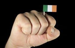 Mężczyzna ręki pięść z irlandczyk flaga odizolowywającą na czerni Fotografia Royalty Free