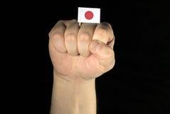 Mężczyzna ręki pięść z japończyk flaga odizolowywającą na czarnym tle Obraz Stock