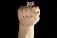 Mężczyzna ręki pięść z Zjednoczone Królestwo flaga odizolowywającą na czerni Fotografia Stock