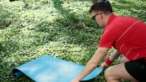 Mężczyzna ręki rozkładają dywanika na trawie dla sportów lub joga Lato s?oneczny dzie? w parku Szeroki k?t Prores, zwolnione temp zbiory