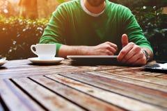 Mężczyzna ręki texting wiadomość na dotyka ekranu pastylce podczas gdy siedzący na balkonu tarasie z roślinami, raca zdjęcia royalty free