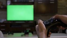 Mężczyzna ręki trzyma gamepad przed chroma klucza zieleni ekranu osocza pokazem bawić się wideo gry na konsoli - zbiory