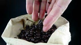 Mężczyzna ręki trzyma kawowe fasole w kanwa worku i niektóre spada puszek, strzału zwolnione tempo na ciemnym tle zbiory