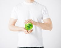 Mężczyzna ręki trzyma zieloną sfery kulę ziemską Fotografia Royalty Free