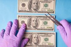 Mężczyzna ręki w rękawiczkach trzyma wyjawionych dolary fotografia stock