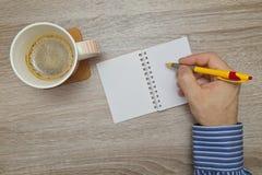Mężczyzna ręki writing plany w notatniku podczas gdy gdy pije kawę Zdjęcia Royalty Free
