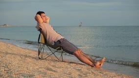Mężczyzna relaksuje na deckchair na plaży zbiory wideo