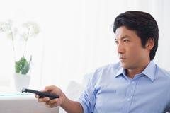 Mężczyzna relaksuje na leżance ogląda tv Fotografia Stock