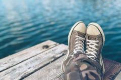Mężczyzna relaksuje na riverbank molu z krzyżować nogami obrazy royalty free