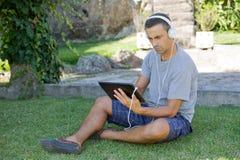 Mężczyzna relaksuje z pastylka komputerem osobistym Zdjęcia Royalty Free