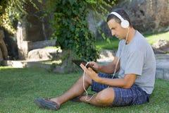 Mężczyzna relaksuje z pastylka komputerem osobistym Fotografia Royalty Free