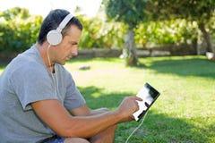 Mężczyzna relaksuje z pastylka komputerem osobistym zdjęcia stock