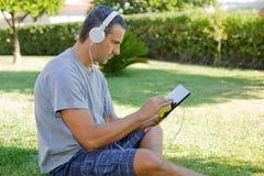 Mężczyzna relaksuje z pastylka komputerem osobistym zdjęcie royalty free