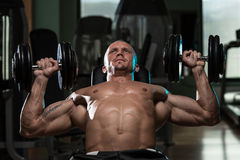 Mężczyzna Robi Dumbbell pochylni ławki prasy treningowi Zdjęcia Royalty Free