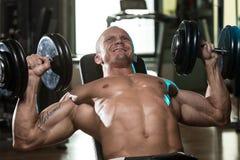 Mężczyzna Robi Dumbbell pochylni ławki prasy treningowi Zdjęcie Stock