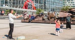 Mężczyzna robi gigantycznym bąblom po środku głównego placu obrazy stock