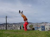 Mężczyzna robi Handstand na wierzchołku na wzgórzu przed budynkami zdjęcie royalty free