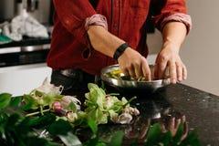 Mężczyzna robi kwiatu arrangment z zielonymi i białymi orhids Zdjęcia Royalty Free