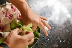 Mężczyzna robi kwiatu arrangment z zielonymi i białymi orhids Zdjęcie Stock