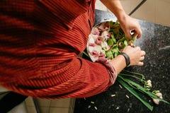 Mężczyzna robi kwiatu arrangment z zielonymi i białymi orhids Obrazy Stock