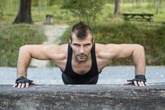 Mężczyzna robi pushups na drewnianej beli. zdjęcia royalty free