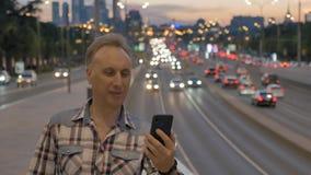 Mężczyzna robi selfie przeciw szerokiej ulicie w wieczór mieście zbiory