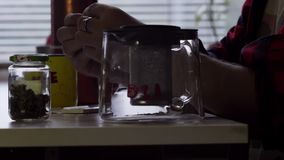 Mężczyzna robi staczającemu się papierosowi przy stołem z dużym kubka i szkła herbacianym garnkiem w kuchni zdjęcie wideo