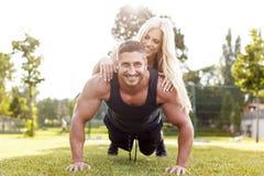 Mężczyzna robi Ups z kobietą na plecy Zdjęcie Stock