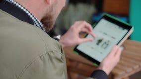 Mężczyzna robi zakupy online, on egzamininuje katalog samiec odziewa w miejscu sklep zbiory