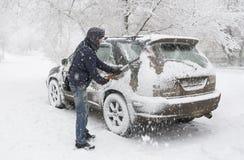Mężczyzna rozjaśnia śnieg od jego samochodu podczas opadu śniegu obrazy stock