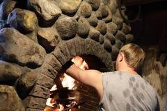 Mężczyzna rozognia ogienia w kuchence obraz royalty free